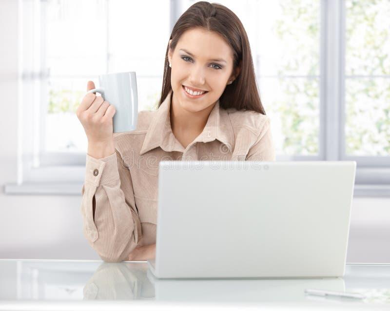 Internet feliz da consultação da mulher em casa fotos de stock