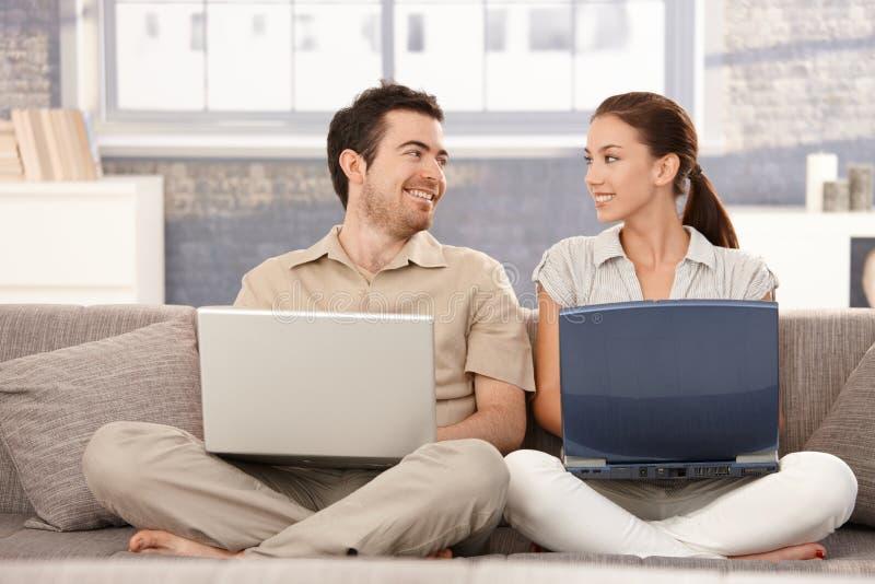 Internet feliz de la ojeada de los pares que tiene sonrisa de la diversión imagen de archivo