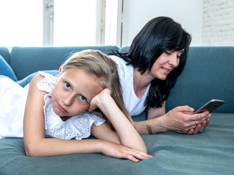 Internet gewöhnte die Mama, die ihr intelligentes Telefon verwendet, das ihr trauriges einsames Kind ignoriert stockfoto