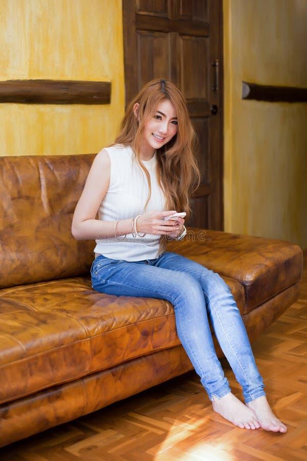 Internet hermoso de la ojeada de la muchacha en un smartphone fotos de archivo libres de regalías