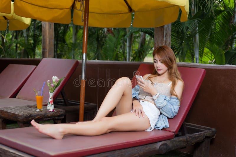 Internet hermoso de la ojeada de la muchacha en un smartphone fotografía de archivo