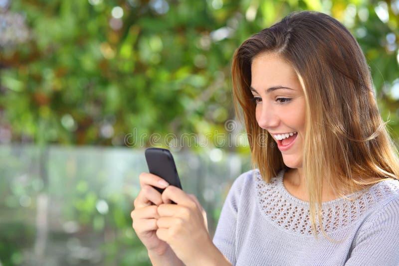 Internet hermoso de la ojeada de la mujer feliz en su teléfono elegante foto de archivo