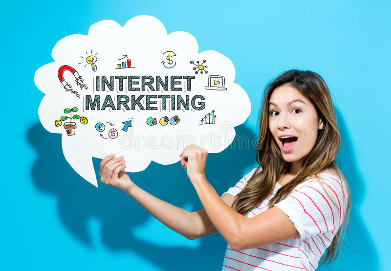 Internet Marketing text with young woman holding a speech bubble. On a blue background royalty free stock images