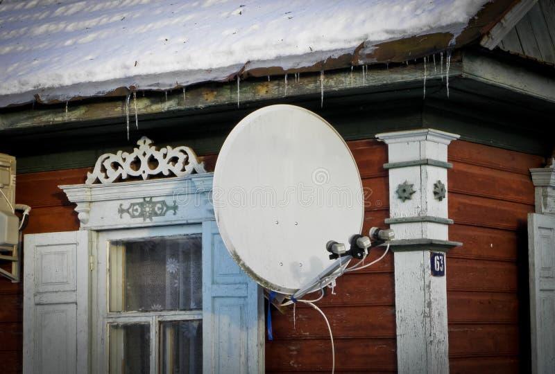 Internet-mededeling en de satellietdieschotel van TV op het dak van het huis bij groene bomenachtergrond wordt geïnstalleerd royalty-vrije stock foto