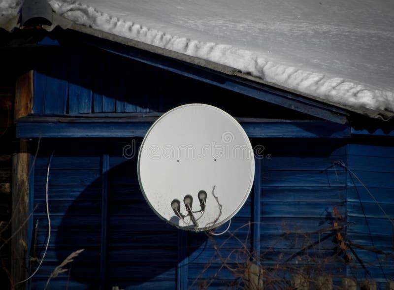 Internet-mededeling en de satellietdieschotel van TV op het dak van het huis bij groene bomenachtergrond wordt geïnstalleerd royalty-vrije stock foto's