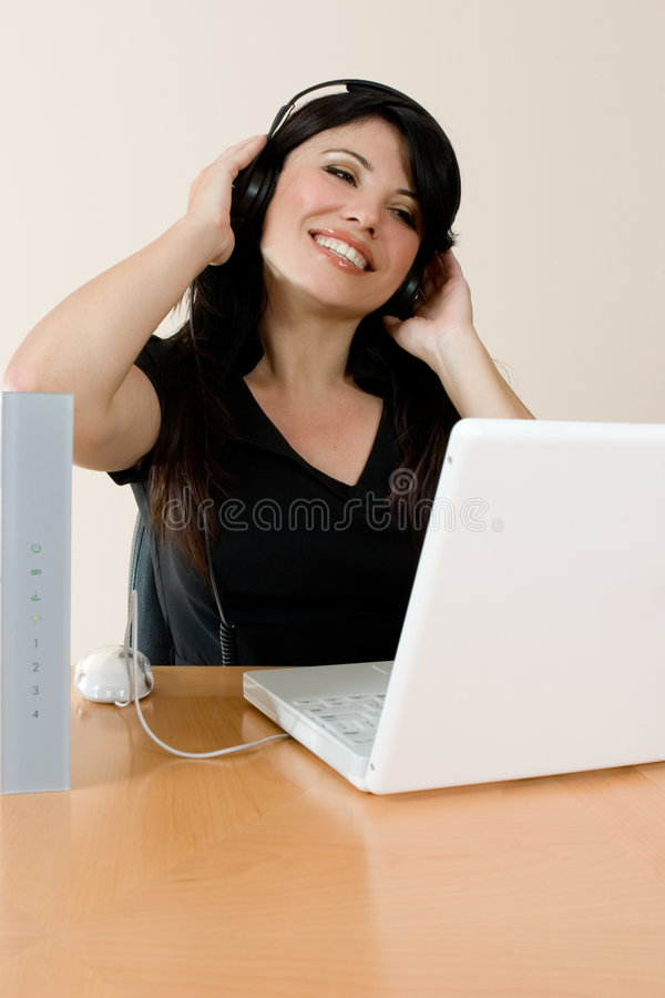 Internet Music. A woman listens to streaming music or video or music downloaded from the internet royalty free stock image