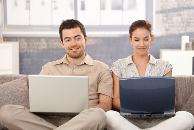 Internet novo da consultação dos pares em casa que sorri imagens de stock