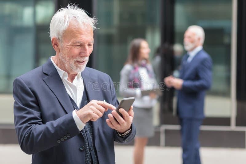 Internet ou mensagem superior feliz da consultação do homem de negócios no telefone esperto foto de stock