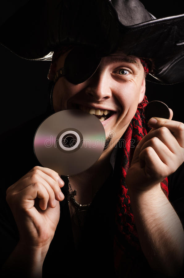 Internet pirate trying CD on the tooth, as the old gold coin. Portrait of a young male pirate with a smile biting CD as checking the quality of old gold coins stock photography