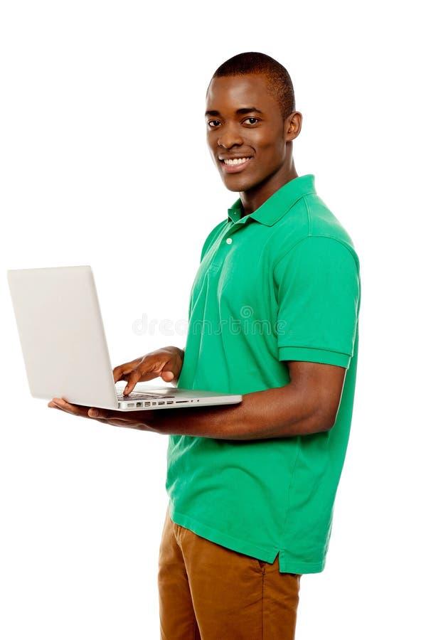 Internet praticante il surfing del tirante adolescente freddo sul computer portatile fotografie stock