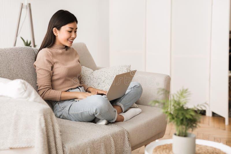 Internet que practica surf de la muchacha adolescente en el ordenador portátil en casa imágenes de archivo libres de regalías
