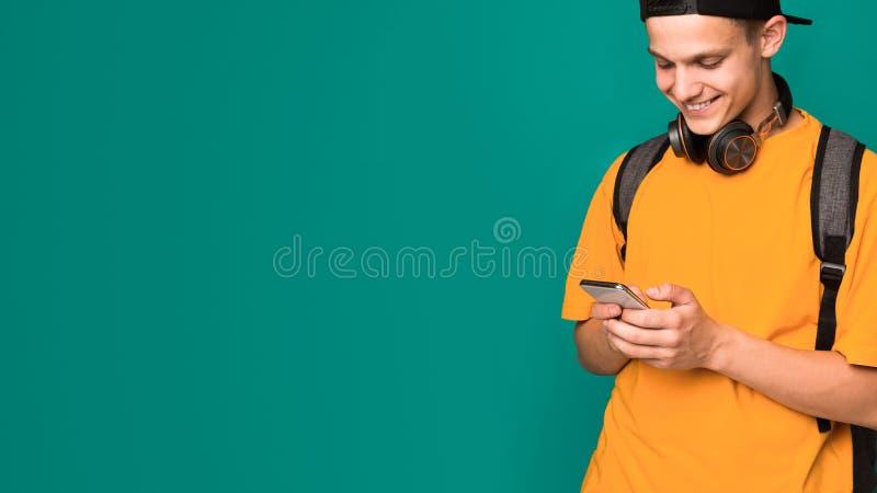Internet que practica surf del adolescente elegante en smartphone sobre fondo foto de archivo