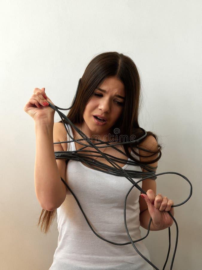 Internet-Süchtiger Abhängigkeit auf Geräten Mädchen eingewickelt in einem Netzkabel auf einem hellen Hintergrund lizenzfreie stockfotos