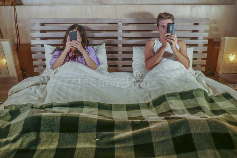 Internet-Süchtigpaare auf dem Bett, das unter Verwendung Social Media-APP am flirtenden Handy und auf Linie Datierung im relation lizenzfreie stockfotografie