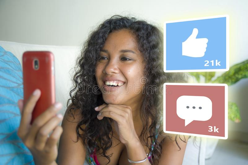 Internet social media app likes and chat comments icons composite on young beautiful and happy mixed ethnicity latin African stock photography