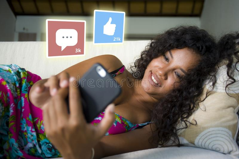 Internet social media app likes and chat comments icons composite on young beautiful and happy mixed ethnicity latin African royalty free stock photo