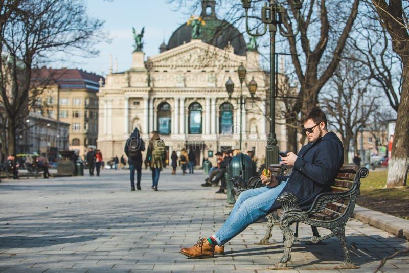 Internet surfant d'hamburger mangeur d'hommes au téléphone se reposant sur le banc photos stock