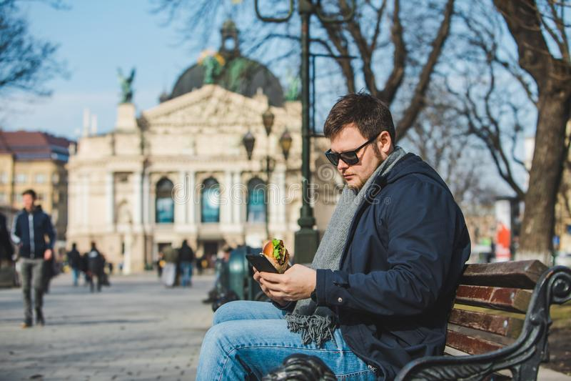 Internet surfant d'hamburger mangeur d'hommes au téléphone se reposant sur le banc images stock