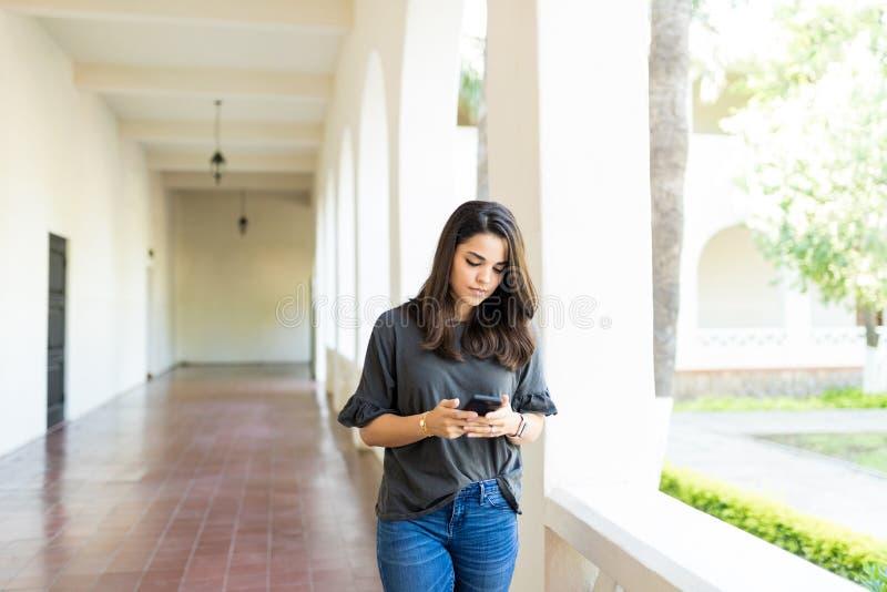 Internet surfant femelle au téléphone portable dans le couloir image stock