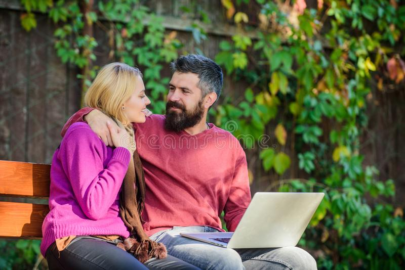 Internet surfing concept. Couple in love notebook consume content. Surfing internet together. Couple with laptop sit. Bench in park nature background. Family royalty free stock image