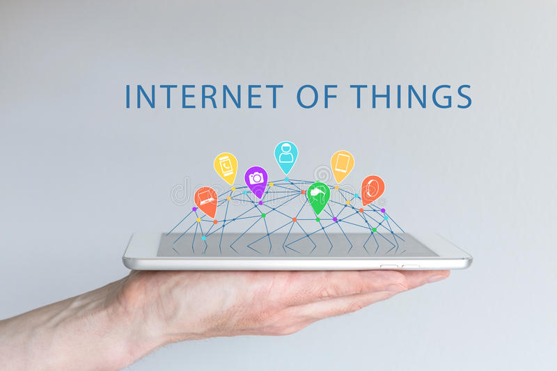 Internet of things (IOT) concept with hand holding smart phone. Connected devices like smart phone, smart watch. Virtual reality, people, camera, wearables and stock photography