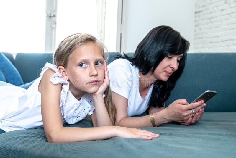 Internet uzależniał się mum używa jej mądrze telefon ignoruje jej smutnego osamotnionego dziecka fotografia royalty free