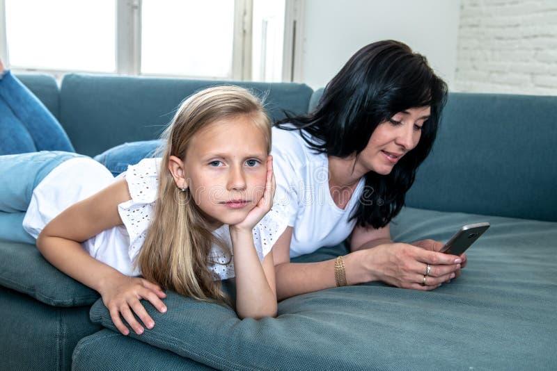 Internet uzależniał się mum używa jej mądrze telefon ignoruje jej smutnego osamotnionego dziecka zdjęcia stock