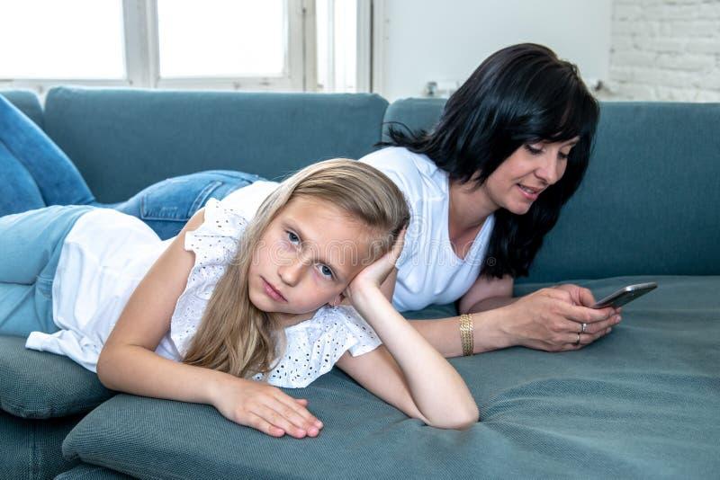 Internet uzależniał się mum używa jej mądrze telefon ignoruje jej smutnego osamotnionego dziecka obraz stock