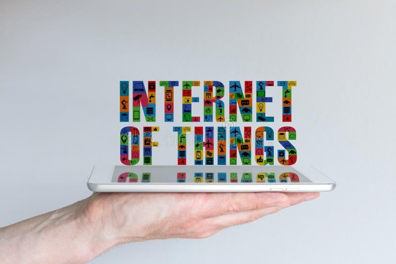 Internet van dingen (IoT) concept Achtergrond met de tablet van de handholding en drijvende tekst in verschillende kleuren en met stock foto's