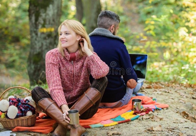 Interneta uzależniony mąż Pracowa? na ?wie?ym powietrzu surfing internetu Szcz??liwa kochaj?ca para relaksuje w parku z laptopem zdjęcie stock