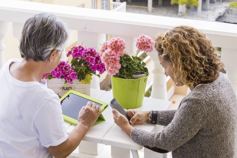 Internetfritidsaktivitet som är utomhus- i terrassen hemma för par av kvinnor som använder teknologi arkivfoton