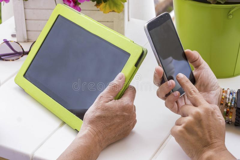 Internetfritidsaktivitet som är utomhus- i terrassen hemma för par av kvinnor som använder teknologi arkivbild