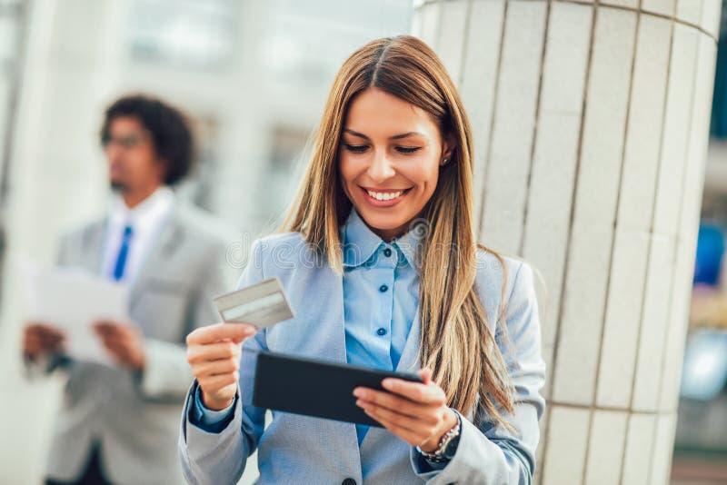 Internetshoppingkvinna direktanslutet med den minnestavlaPC och kreditkorten arkivbilder