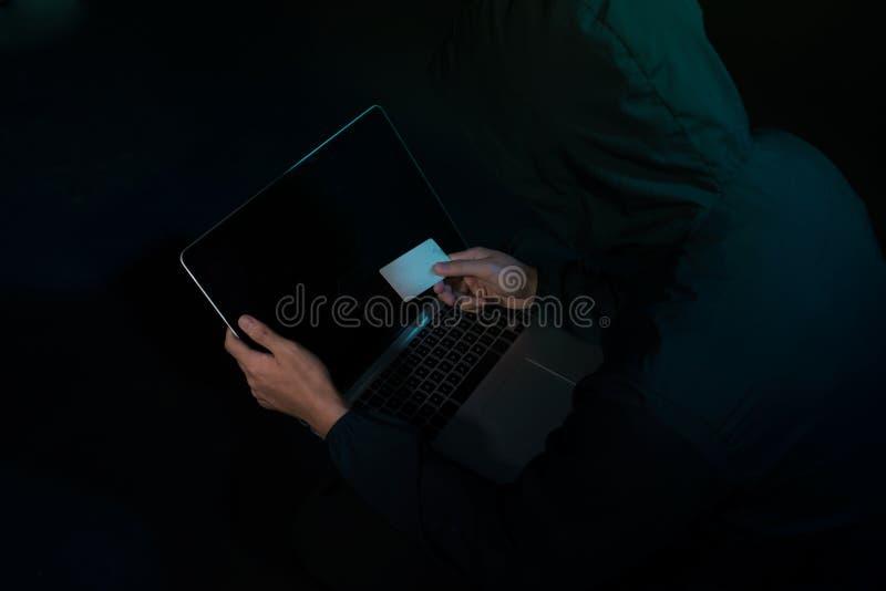 Internetstöld - en man som rymmer en kreditkort, medan suttet bak en bärbar dator arkivbilder