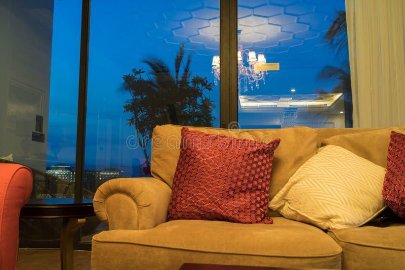 Interni dell'hotel di vacanza con il sofà, sedia, porta contro il twili immagini stock libere da diritti