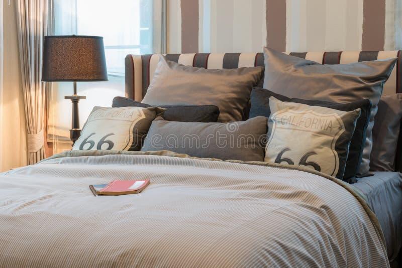 Interno accogliente della camera da letto con i cuscini di marrone scuro e la lampada di lettura - Letto con cuscini ...