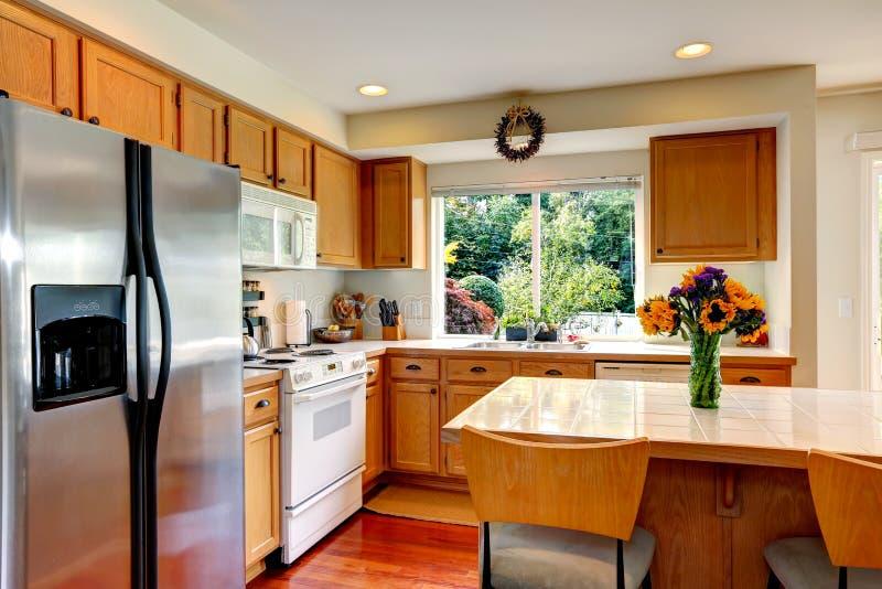 Interno accogliente della cucina con l'isola e la finestra fotografia stock