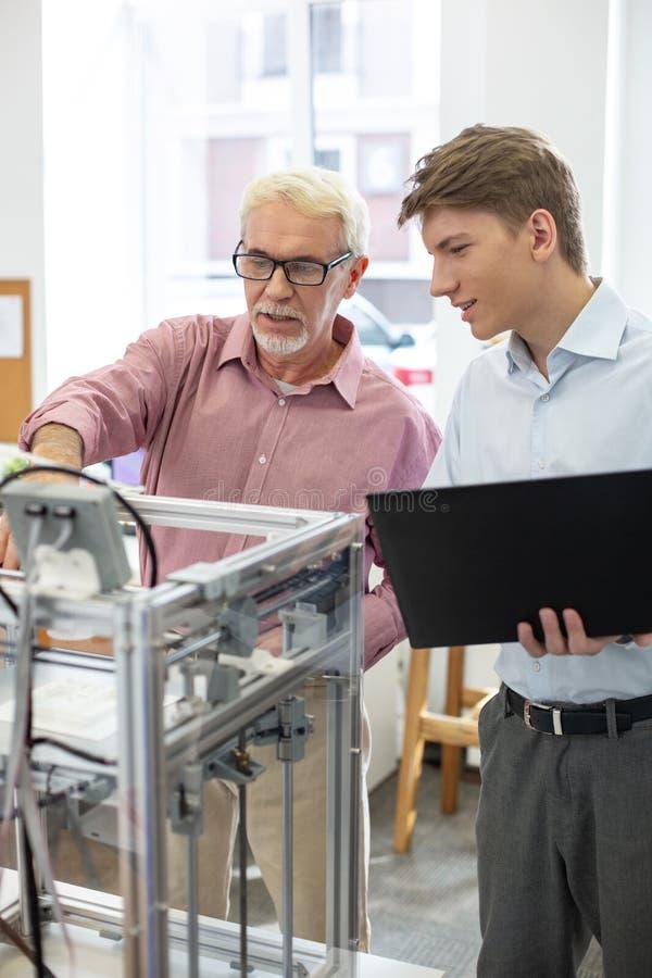Interno agradable y su supervisor que cambian configuraciones de la impresora 3D imagenes de archivo