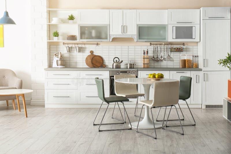 Interno alla moda della cucina con il tavolo da pranzo immagini stock libere da diritti