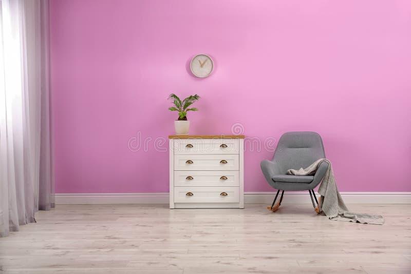 Interno alla moda della stanza con il cassettone e la sedia di oscillazione fotografia stock libera da diritti