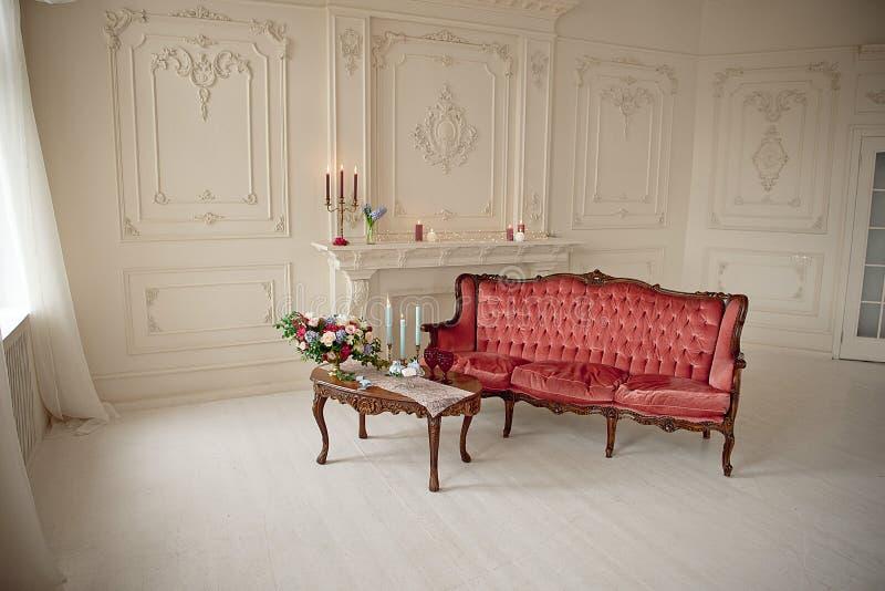 Interno barrocco di stile con il sofà e la tavola di lusso rossi fotografia stock libera da diritti