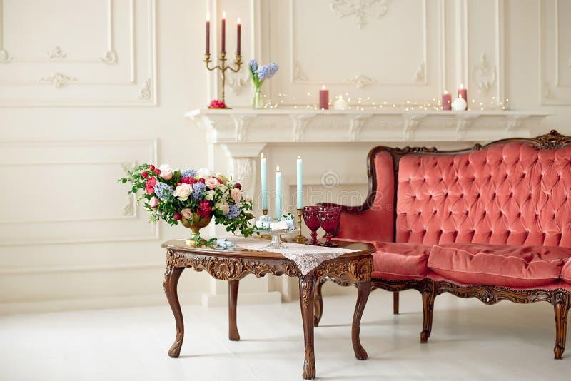 Interno barrocco di stile con il sofà e la tavola di lusso rossi fotografia stock
