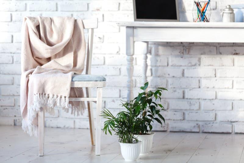 Interno bianco con la sedia, la coperta e la piccola tavola immagine stock