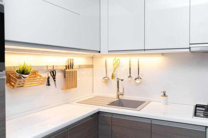 Interno bianco della cucina di lucentezza con illuminazione di piano di lavoro fotografia stock