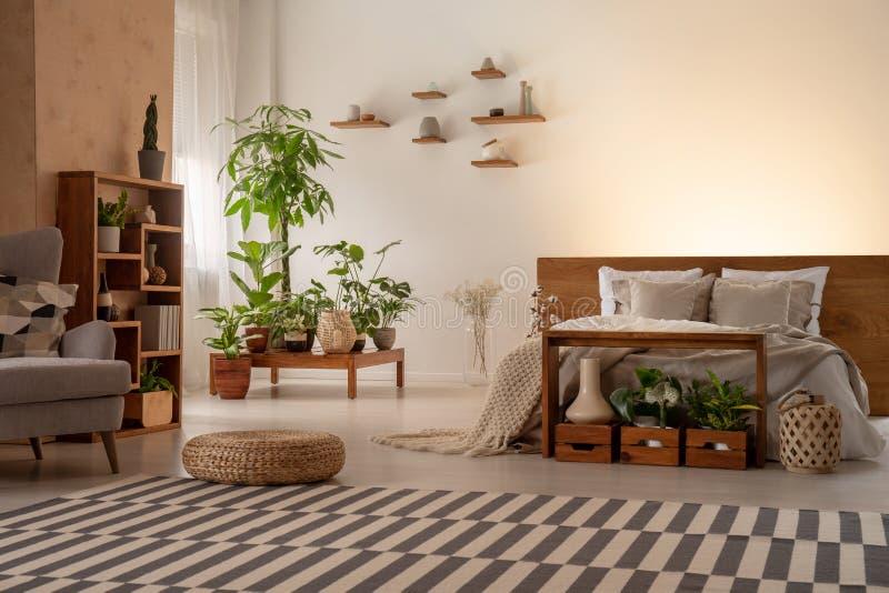 Interno caldo della camera da letto con le piante, scaffali, coperta a strisce, pouf, b immagini stock libere da diritti