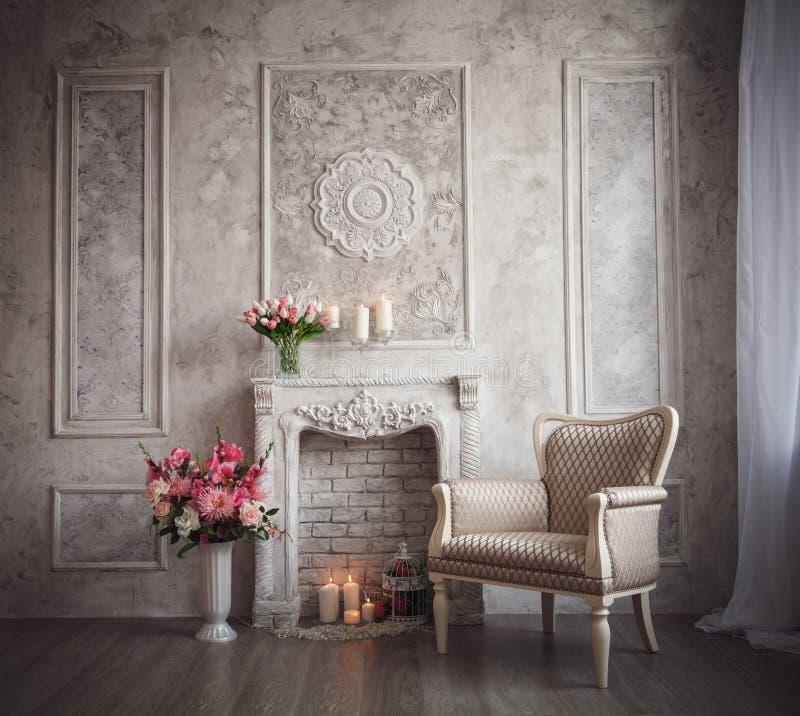 Interno con il fondo, il camino ed i fiori grigi del lavoro di traforo fotografie stock