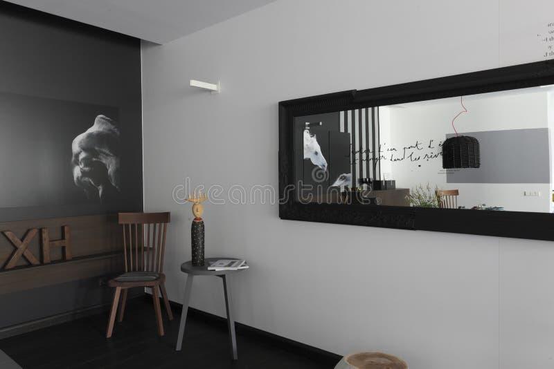 Interno con le immagini dei cavalli sulla parete monocromatica immagini stock libere da diritti