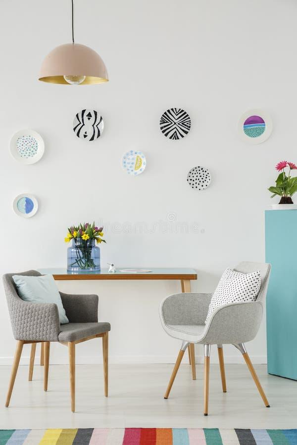 Interno creativo del salone con i piatti sulla parete, tavola, gr immagine stock