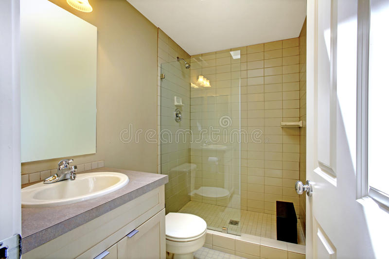 Interno cremoso piacevole del bagno con la doccia di vetro e gabinetto bianco con lo specchio immagini stock
