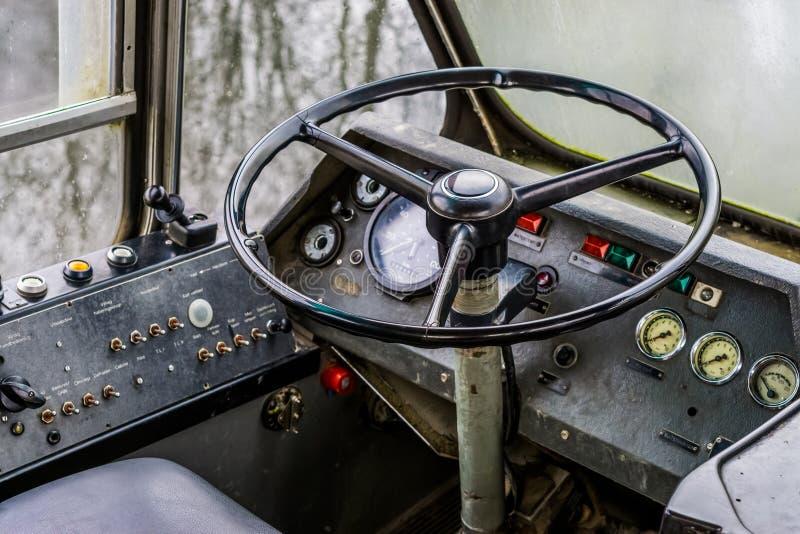 Interno d'annata molto vecchio di vecchio scuolabus del temporizzatore, cruscotto con il volante di retro veicolo fotografia stock